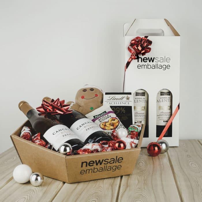 Firmagaver med logotryk. 6-kantet gavekurv i natur med vin, chokolade, nødder og julepynt. Hvid vinkarton med vin og rødt gavebånd.