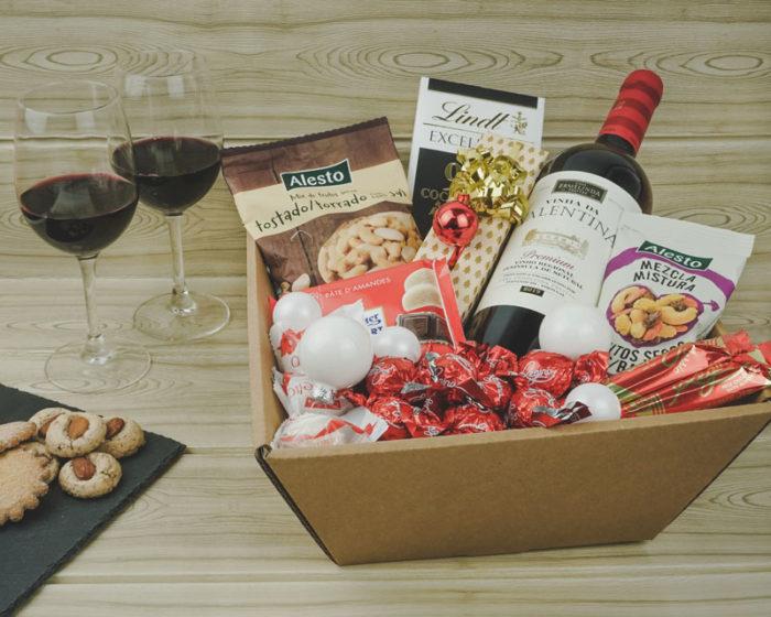 Julegave inspiration med lille gavekurv i natur/brunt pap. Pakket med vin, nødder, chokolade og julepynt