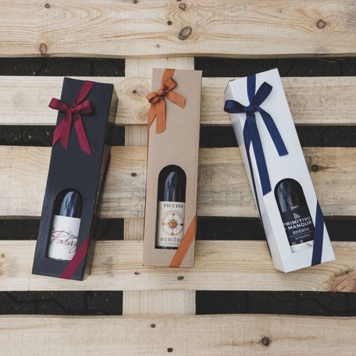 Vinkartoner i blanksort, natur og hvidt pap til 1 flaske, med bordeaux, orange og blåt gavebånd.