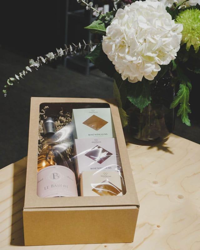 Lille gaveæske med rude i natur/brunt pap med rose vin og vingummier