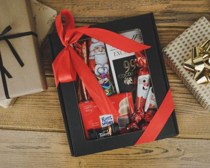 Julebillede af XS gaveæske med rude i matsort pap med chokolade og rødt gavebånd