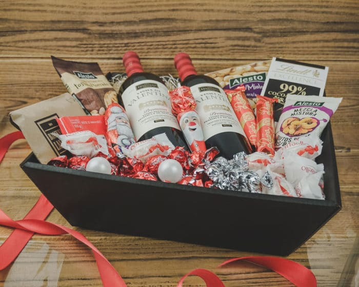 Julebillede med mellem gavekurv i matsort pap, med med vin, nødder, lakrids, chokolade og julepynt.