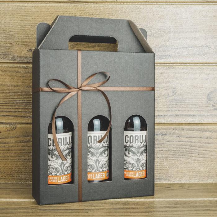 Ølkarton i matsort pap til 3 flasker a 33 cl. med brunt gavebånd og træbaggrund