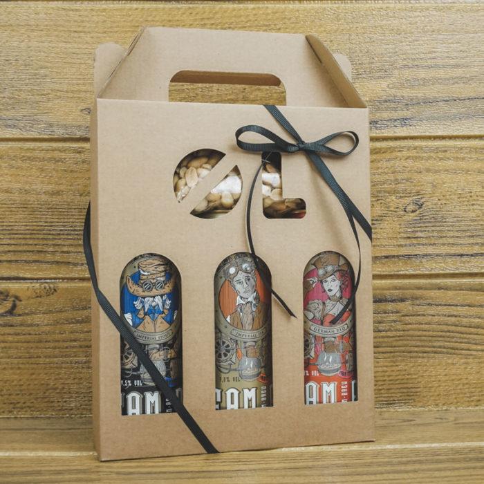 Ølkarton i naturfarvet pap med 3 dåseøl og nødder med sort gavebånd og træbaggrund