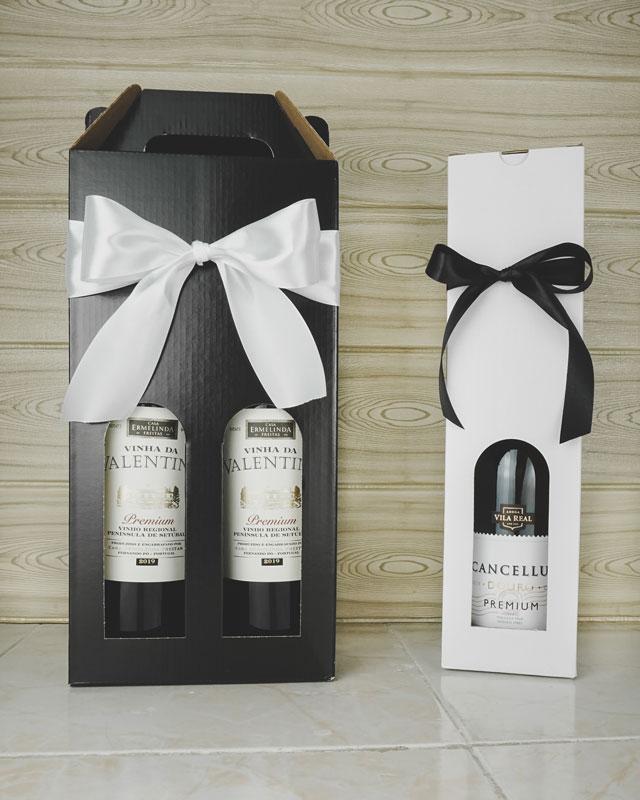 Vinkarton i blanksort pap til 2 flasker og vinkarton i hvidt pap til 1 flaske. Pakket med vin og gavebånd.