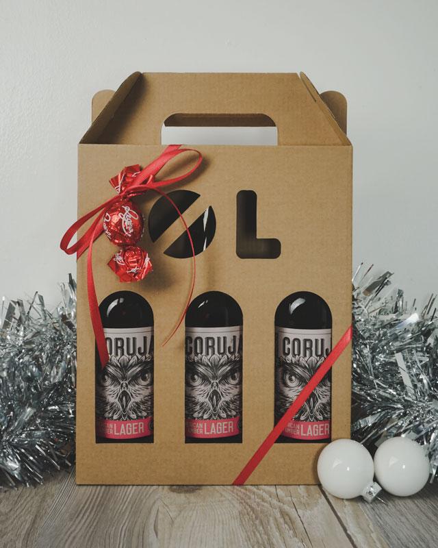 Julebillede af ølkarton i natur til 3 flasker a 33 cl. med ølstans, med øl, rødt gavebånd og julepynt