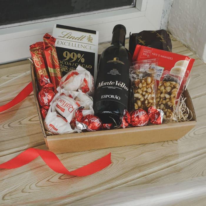 Værtindebakke i natur i vindueskarm pakket med lille vin, chokolade og nødder