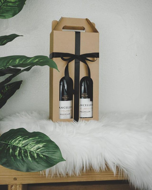 Vinkarton i naturfarvet pap til 2 flasker med sort gavebånd og plante